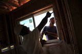 10 September 2012 - Workers install a window in a new home at a construction site only a few hundred metres from the USA border, and Washington State, in Surrey, B.C., Canada. Credit: Adrian Brown - N49Photo.