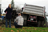 05 November 2012 - People look at an overturned truck at the side of Highway 99, in Surrey, B.C., Canada. While an investigation will take place, it is believed that the right front tire of the truck blew out, causing the truck to veer off the shoulder, rolling onto its side in a grassy area beside the highway. The driver was unhurt at the scene. Credit: Adrian Brown - N49Photo.