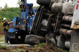 05 November 2012 - A truck tow operator attends the scene of an overturned truck, on Highway 99, in Surrey, B.C., Canada. While an investigation will take place, it is believed that the right front tire of the truck blew out, causing the truck to veer off the shoulder, rolling onto its side in a grassy area beside the highway. The driver was unhurt at the scene. Credit: Adrian Brown - N49Photo.