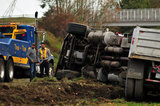 05 November 2012 - The driver (right) of an overturned truck on Highway 99, speaks to another man beside the scene of the accident, in Surrey, B.C., Canada. While an investigation will take place, it is believed that the right front tire of the truck blew out, causing the truck to veer off the shoulder, rolling onto its side in a grassy area beside the highway. The driver was unhurt at the scene. Credit: Adrian Brown - N49Photo.