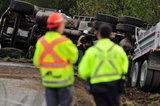 05 November 2012 - An RCMP officer talks to another man at the scene of an overturned truck, on Highway 99, in Surrey, B.C., Canada. While an investigation will take place, it is believed that the right front tire of the truck blew out, causing the truck to veer off the shoulder, rolling onto its side in a grassy area beside the highway. The driver was unhurt at the scene. Credit: Adrian Brown - N49Photo.