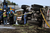 05 November 2012 - Workers attach cables to an overturned truck in preparation to position it back on its wheels, on Highway 99, in Surrey, B.C., Canada. While an investigation will take place, it is believed that the right front tire of the truck blew out, causing the truck to veer off the shoulder, rolling onto its side in a grassy area beside the highway. The driver was unhurt at the scene. Credit: Adrian Brown - N49Photo.