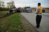05 November 2012 - The driver of an overturned truck speaks on the phone, beside the scene of the accident on Highway 99, in Surrey, B.C., Canada. While an investigation will take place, it is believed that the right front tire of the truck blew out, causing the truck to veer off the shoulder, rolling onto its side in a grassy area beside the highway. The driver was unhurt at the scene. Credit: Adrian Brown - N49Photo.