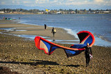 25 September 2013 - White Rock, B.C., Canada - A man carries his kiteboard equipment, as others fly their kites and kiteboard on East Beach, on the Semiahmoo First Nation reserve just south of the city of White Rock. Drayton Harbor and the US coastline are seen in the distance, as well as US Customs control in Blaine, WA, far left. Photo Credit: Adrian Brown / Sipa Press.