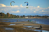 25 September 2013 - White Rock, B.C., Canada - People fly their kiteboard kites on East Beach, on the Semiahmoo First Nation reserve just south of the city of White Rock. Drayton Harbor and the US coastline are seen in the distance, as well as the Peace Arch monument (straddling the Canada, US border) and US Customs control in Blaine, WA, centre. Photo Credit: Adrian Brown / Sipa Press.