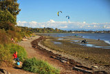 25 September 2013 - White Rock, B.C., Canada - People fly their kites and kiteboard on East Beach, on the Semiahmoo First Nation reserve just south of the city of White Rock. Drayton Harbor and the US coastline are seen in the distance, as well as US Customs control in Blaine, WA, centre right. Photo Credit: Adrian Brown / Sipa Press.