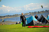 25 September 2013 - White Rock, B.C., Canada - Two men pack up their kiteboard equipment, as others fly their kites and kiteboard on East Beach, on the Semiahmoo First Nation reserve just south of the city of White Rock. Drayton Harbor and the US coastline are seen in the distance, as well as US Customs control in Blaine, WA, far left. Photo Credit: Adrian Brown / Sipa Press.